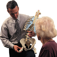 MD showing patient human spine model
